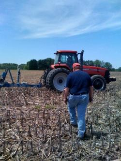 Steve Waddle walks over to his son Mark, busy planting conventional soybean seed.