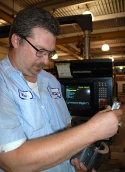 Mike Kostica checks the tolerances on a part at  Astro Manufacturing in Eastlake.
