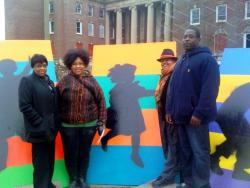 Artists Anjelica Pozo, Cheryl Jones, Anna Arnold, Doente Sanderfer pose with boards to cover the broken windows of old St.Luke's Hospital