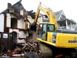 An excavator razes a derelict home in Cleveland (pic by Brian Bull).