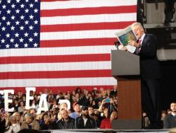 Bill Clinton reads USA Today excerpts about GM profits and Mr. Obama's and Chris Christie's storm relief efforts. Photo by Nick Castele.