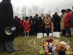 East Cleveland Mayor Gary Norton and others pray near the spot where Timothy Russell and Malissa Williams were killed.