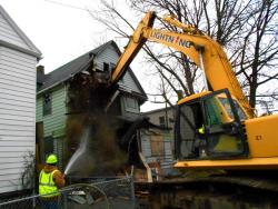 An excavator begins ripping and crushing a Morton Avenue house (photo by Brian Bull).