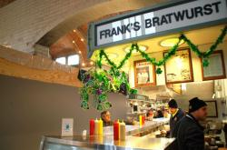 A gray, playwood wall covering up fire damage looms over Frank's Bratwurst stand
