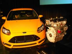 A Ford vehicle flanked by the new 2.0 liter EcoBoost engine at today's press conference (pic by Brian Bull)