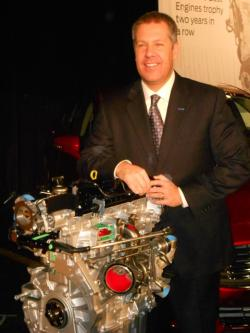 Ford's President of the Americas, Joe Hinrich, poses next to a new 2.0 liter EcoBoost engine (pic by Brian Bull)