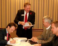 Representatives of Drury Southwest Inc. sign bidding agreement with CBRE auctioneers. (pic by Brian Bull)