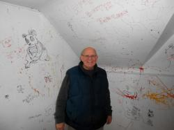 Realtor and banker Edward Bugos stands in one of its bedrooms, surrounded by graffitti (pic by Brian Bull)