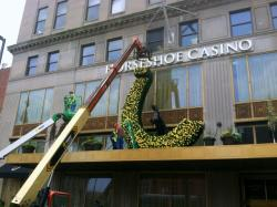 Workers mount a large horseshoe adorned with yellow roses on the front of the Horseshoe Casino (pic by Brian Bull).