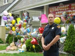 A police officer stands outside the home of Amanda Berry's sister's house, where she arrived today (pic by Brian Bull)