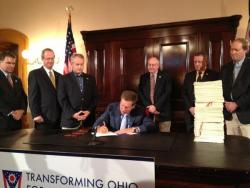 Gov. John Kasich signs the Ohio budget into law in June 2013. (Karen Kasler / ideastream)