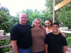 The Byrne family poses near their vegetable garden. From left to right: David, Laura, Maritza, and D.J.