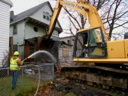 An excavator smashes apart a Cleveland house (WCPN stock photo by Brian Bull)