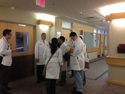 Doctors and students talk quietly outside a patient room in University Hospitals Lerner Tower.