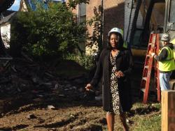 Council President Joy Jordan walks back from an excavator after taking a ceremonial swipe at a vacant building.