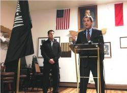Sen. Sherrod Brown speaks in Cleveland, as retired Air Force / Air National Guard Col. Robert Schuett looks on.