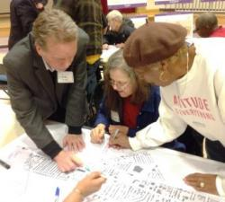 CWRU's Mark Chupp write on a map with Patricia Blochowiak and Elsie Whitfield. (Nick Castele / ideastream)