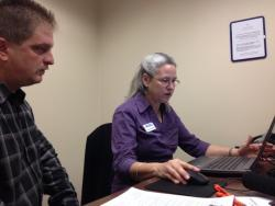 Rachel Rosen DeGolia helps a Cuyahoga County man sign up for healthcare. (Sarah Jane Tribble / ideastream)