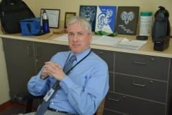 Thomas O'Grady poses for a photo in his school office. (Nick Castele / ideastream)