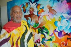 Walter Allen Rogers Jr. poses for a photo in front of a work of art in his apartment. (Nick Castele / ideastream)