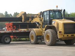 A heavy loader prepares to carry steel pipes used in the fracking process. (photo by Brian Bull)