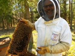 Joel Leachko examines one of his hives (photo by Brian Bull)