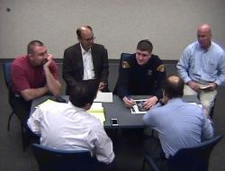 Officer Brelo talks with investigators, flanked by an attorney and union officials. (Image from Attorney General video)