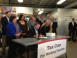 Gov. Kasich signs his budget update bill at a food bank. (Karen Kasler / Statehouse News Bureau)