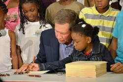Gov. Kasich asks a child to dot the 'i' in his signature. (Nick Castele / ideastream)