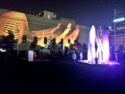 Abstract patterns are projected on the side of Public Hall while an eternal flame sculpture undulates with rainbow hues