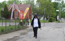 In the early morning hours of a local charity walk, advocates advertise Medicaid enrollment as a woman walks to the fest