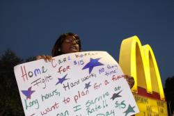 Ashley Mills, 25, holds a sign at an early morning rally to raise pay. As a full-time home care worker for the past 3 ye