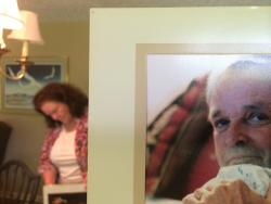 Kathy Schreiber searches for pictures of Bob. In front, a picture of Bob from earlier days.