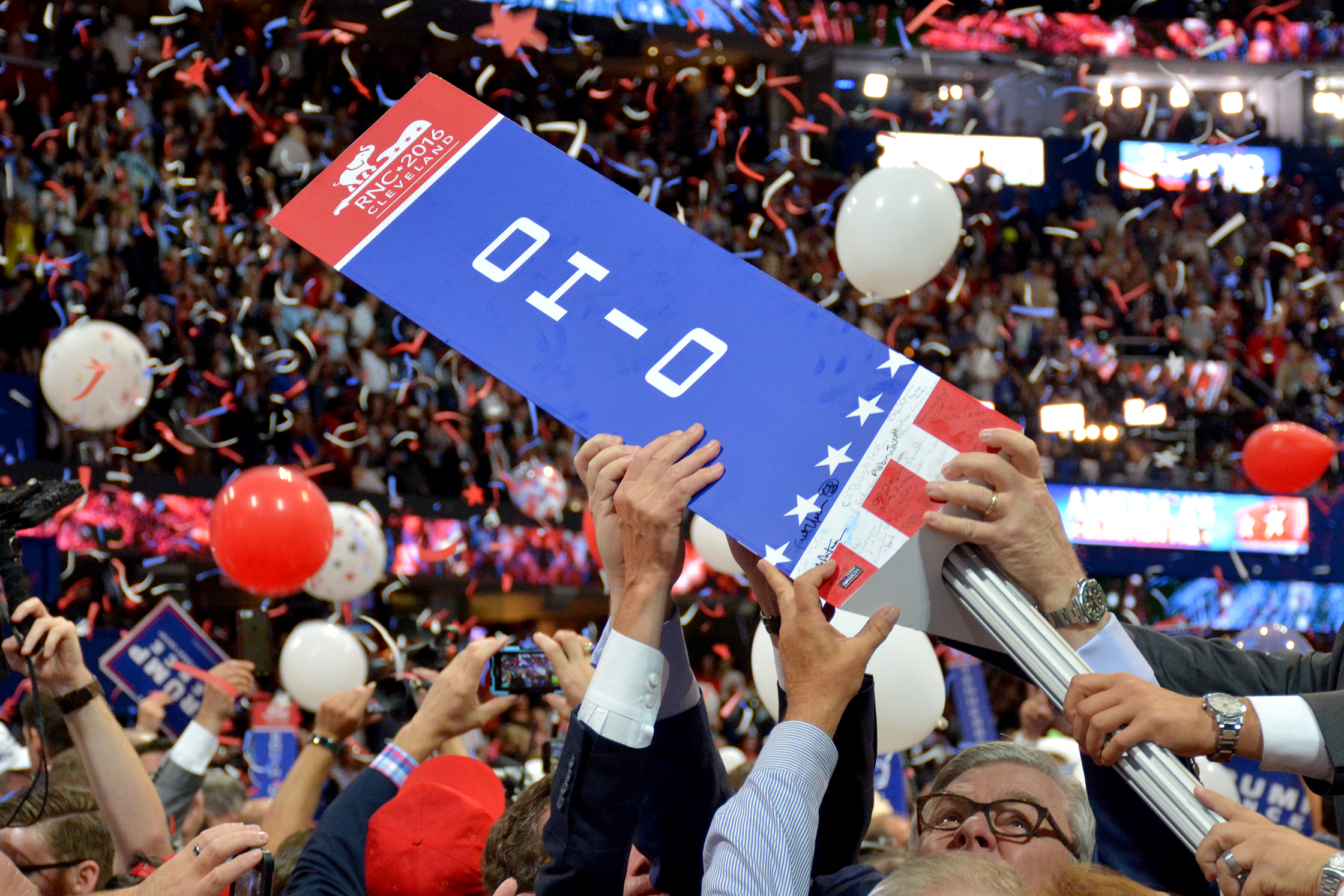 Ohio Republicans remove their state's sign at the end of the party's convention in Cleveland. [Nick Castele / ideastream]