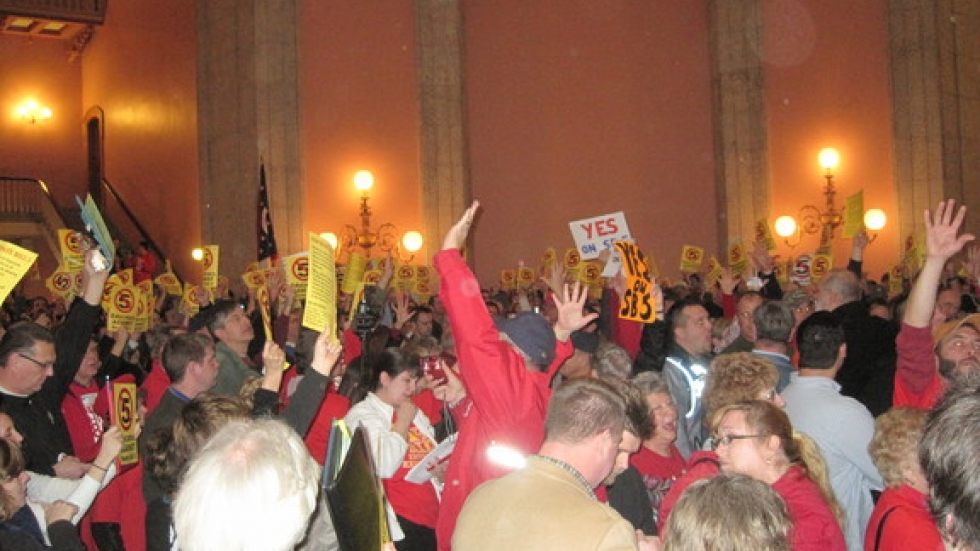 Groups in statehouse rotunda duel to support their sides of debate.