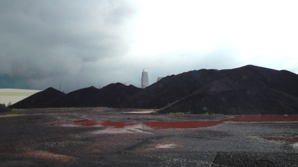 The Key Tower rises in the distance behind a pile of iron ore pellets. (Nick Castele / ideastream)