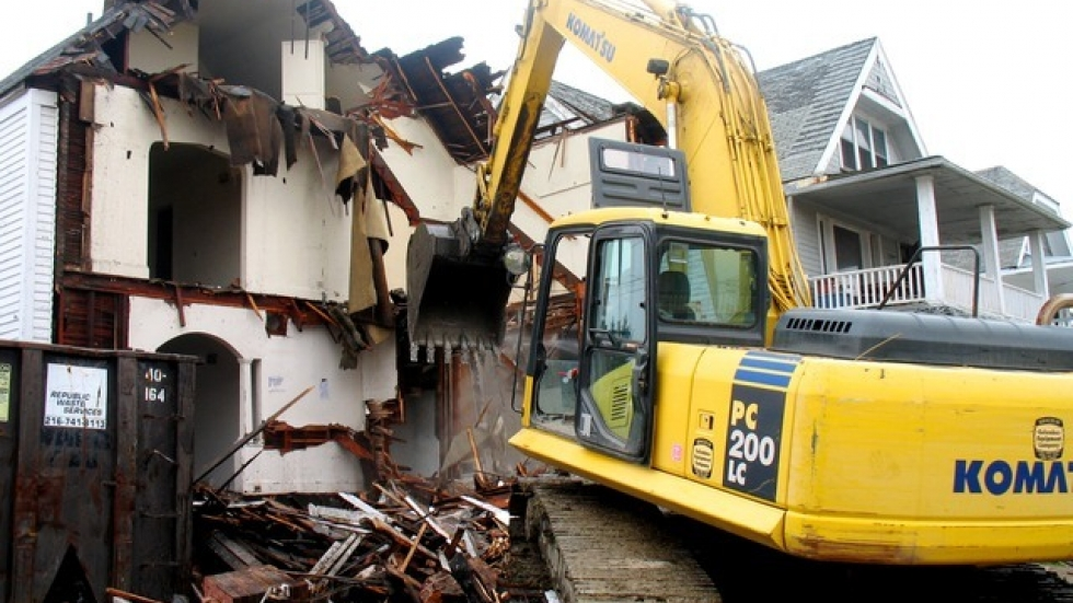 An excavator razes a derelict home in Cleveland. (ideastream file photo by Brian Bull).