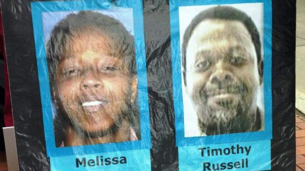 Images of Malissa Williams and Timothy Russell appear on a placard carried by protesters of the shooting. (Nick Castele)