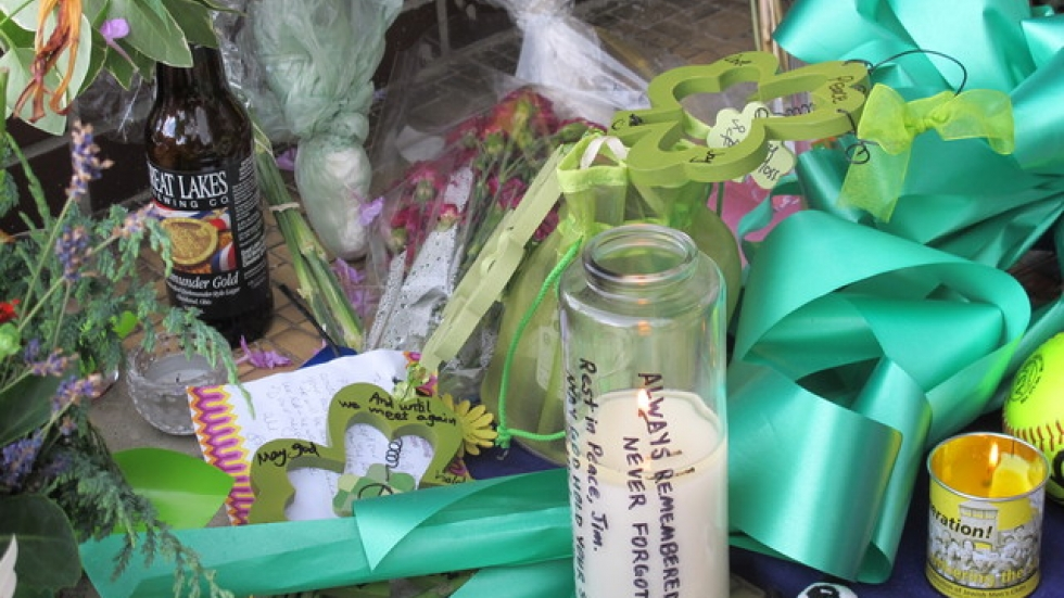 Someone added a beer bottle among the flowers and candles at the makeshift memorial.