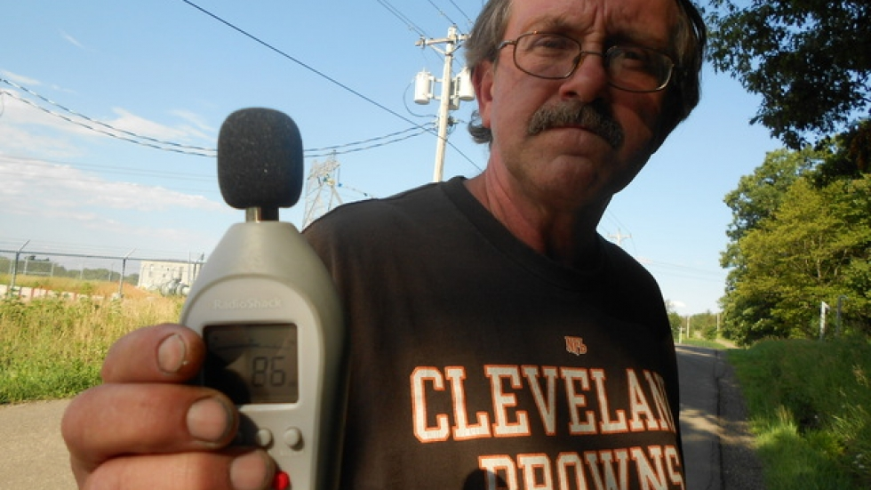 At his property line, Frank Brothers holds a sound meter reading 86 decibels. The noise runs 24/7.