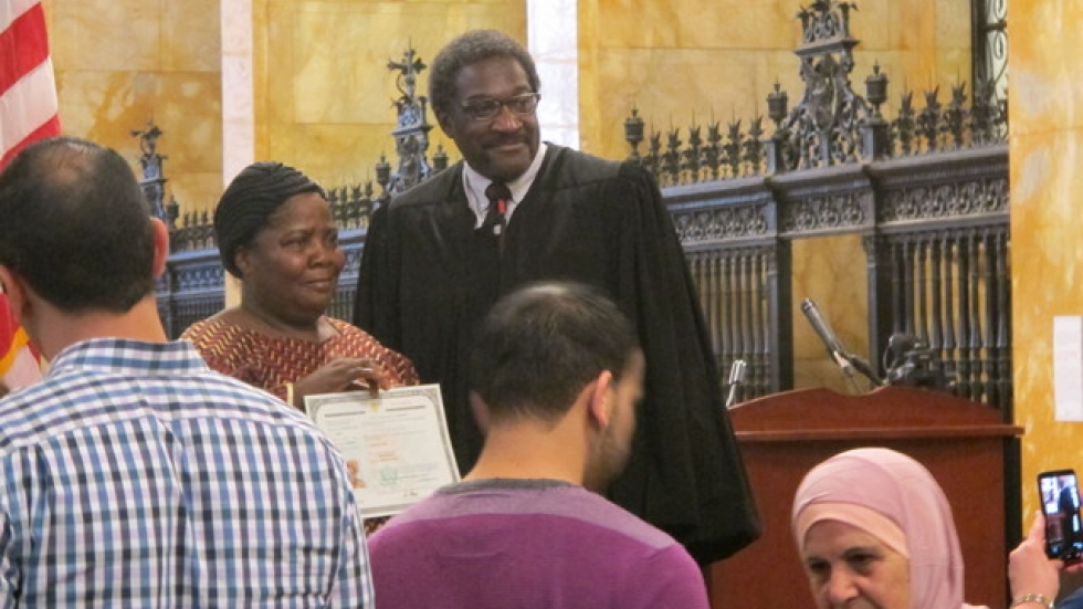 Newly-naturalized citizens smile with Judge Solomon Oliver (pic: Brian Bull)