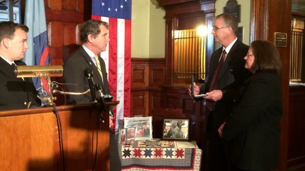 From left, a Navy officer and Senator Sherrod Brown speak with TJ and Lori Eisenbraun, near a table filled with photos of Larry Eisenbraun.