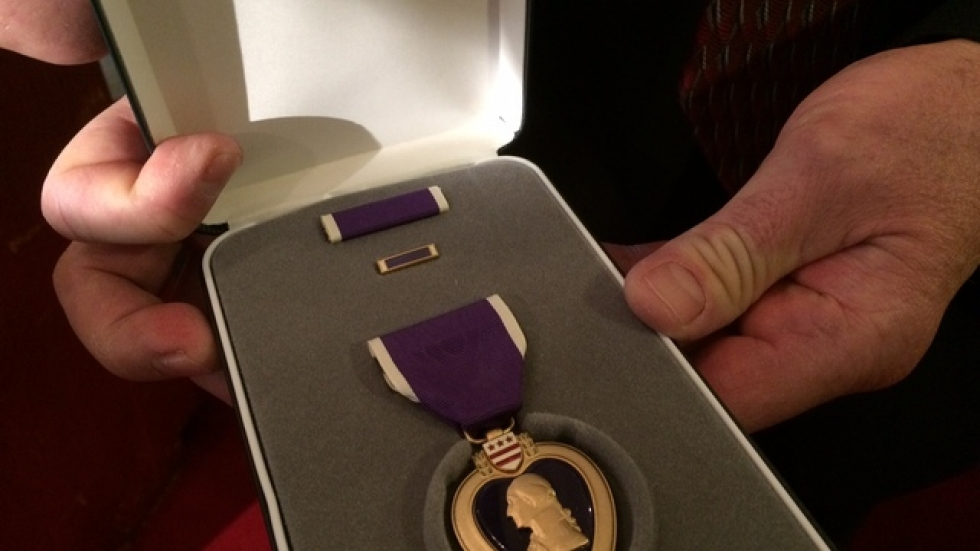 TJ Eisenbraun holds the Purple Heart his younger brother earned during the Vietnam War.