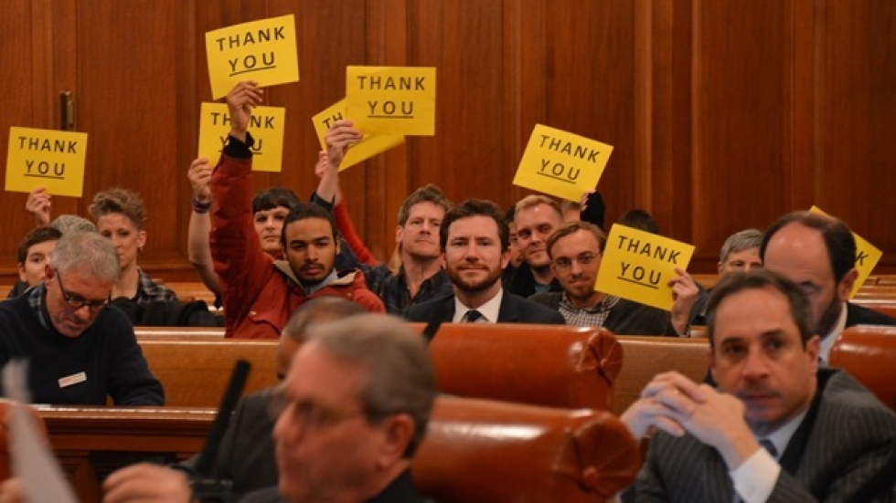 Supporters of Cleveland's new transgender protections hold signs at the end of the council meeting. (Nick Castele)