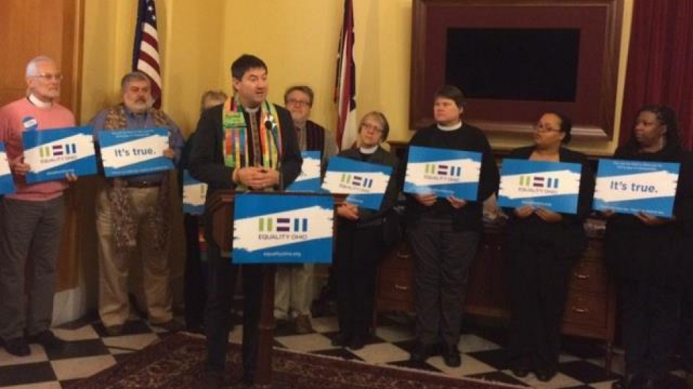 LGBT advocates hold Equality Ohio signs at a press conference. (Jo Ingles / Ohio Public Radio)