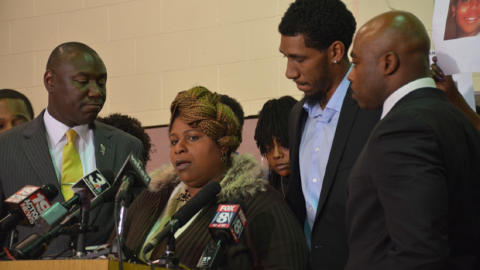 Tamir Rice's mother, Samaria, speaks to reporters as Tamir's father, Leonard Warner, next right, bows his head.