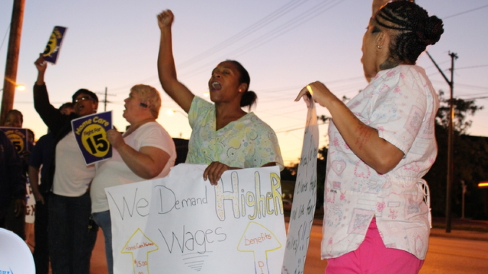 Home care workers Artheta Peters, center, and Jasmine Almodovar, right, rally for higher wages in Cleveland.