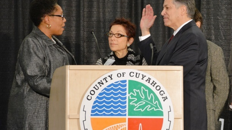 U.S. Rep. Marcia Fudge administers the oath of office to Armond Budish as his wife, Amy, looks on. (Nick Castele)