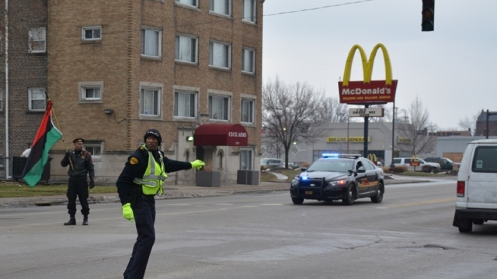 An East Cleveland police officer directs motorists during a protest over a broken traffic light. (Nick Castele)
