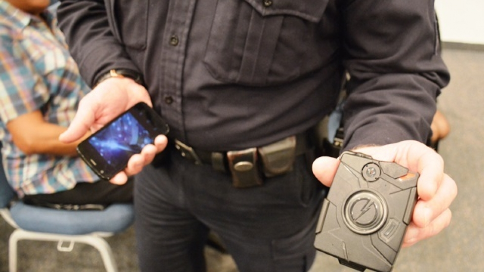 Sgt. Todd Melzer holds a body camera, which officers can attach to the breast pocket of their uniforms. (Nick Castele)